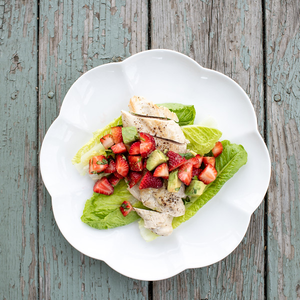 Chicken Cutlets with Strawberry Avocado Salsa on a white plate and blue background.