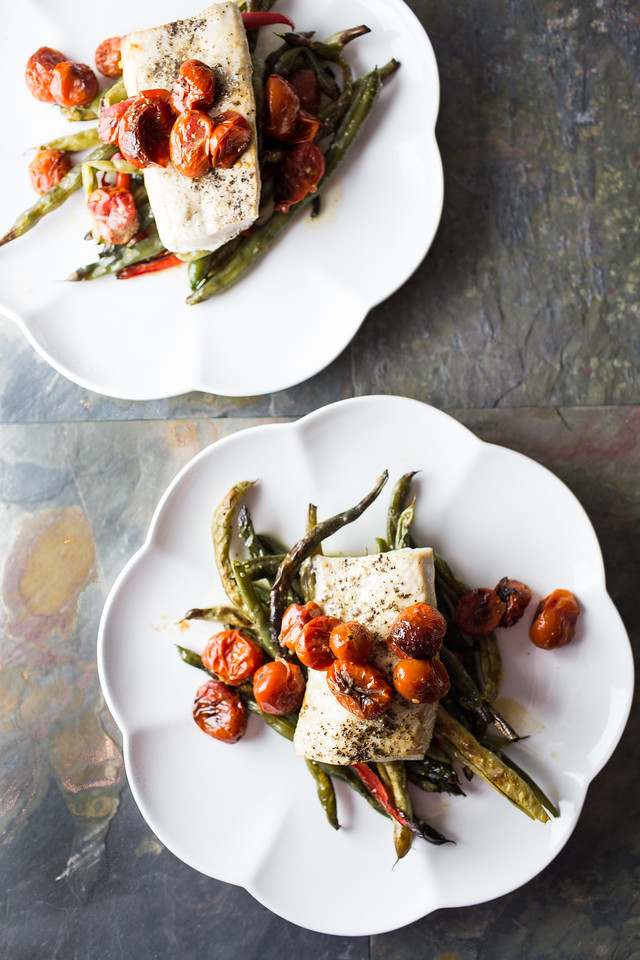 Two plates with mahi mahi and green beans and tomatoes
