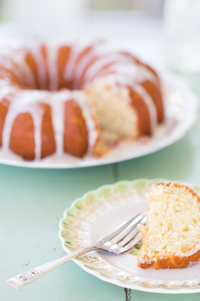Slice of lemon bundt cake on a plate with the whole cake behind it.