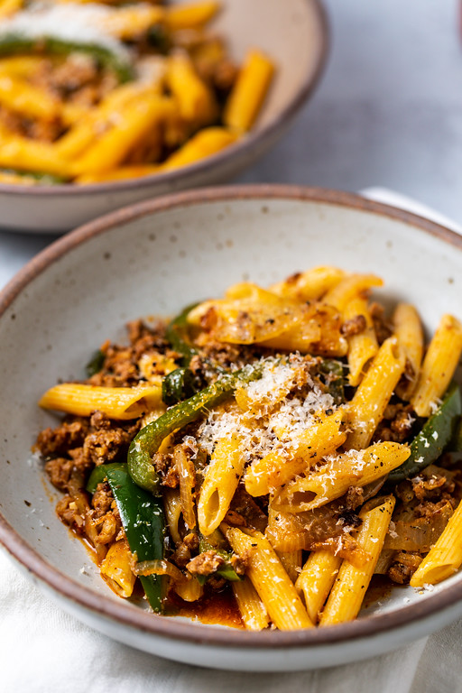 Gray bowl filled with pasta, sausage and peppers and topped with grated cheese.