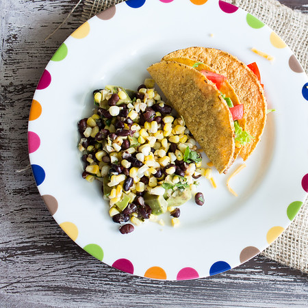 A plate with corn, avocado and black bean salad and a hard taco.