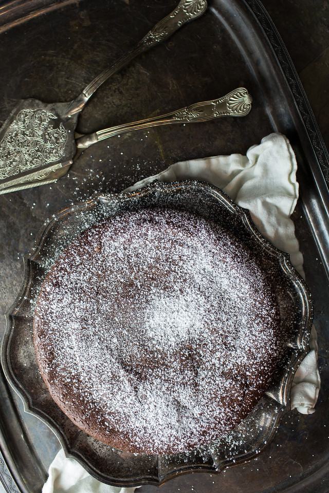Dark chocolate cake on an old serving tray with vintage serving utensils.