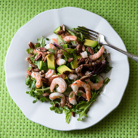 Plate of shrimp salad on a green background