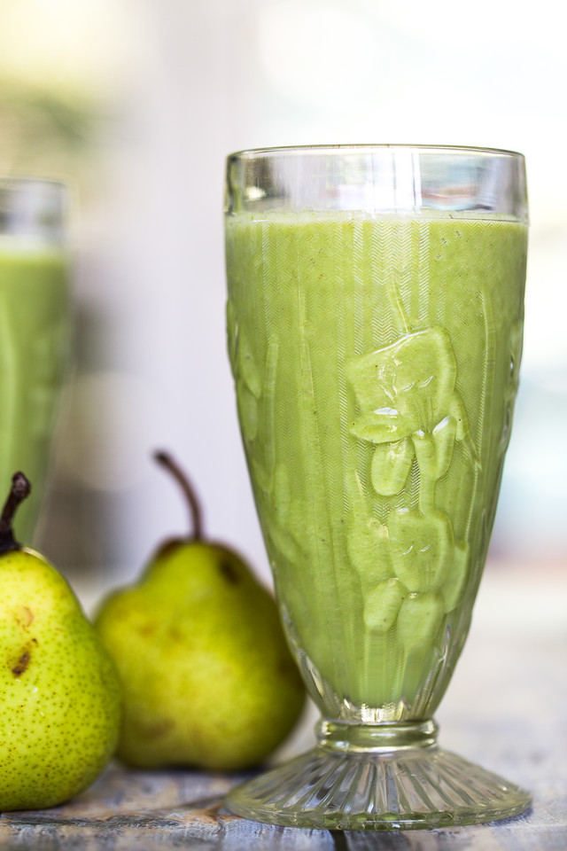 Glass filled with a green smoothie with two pears