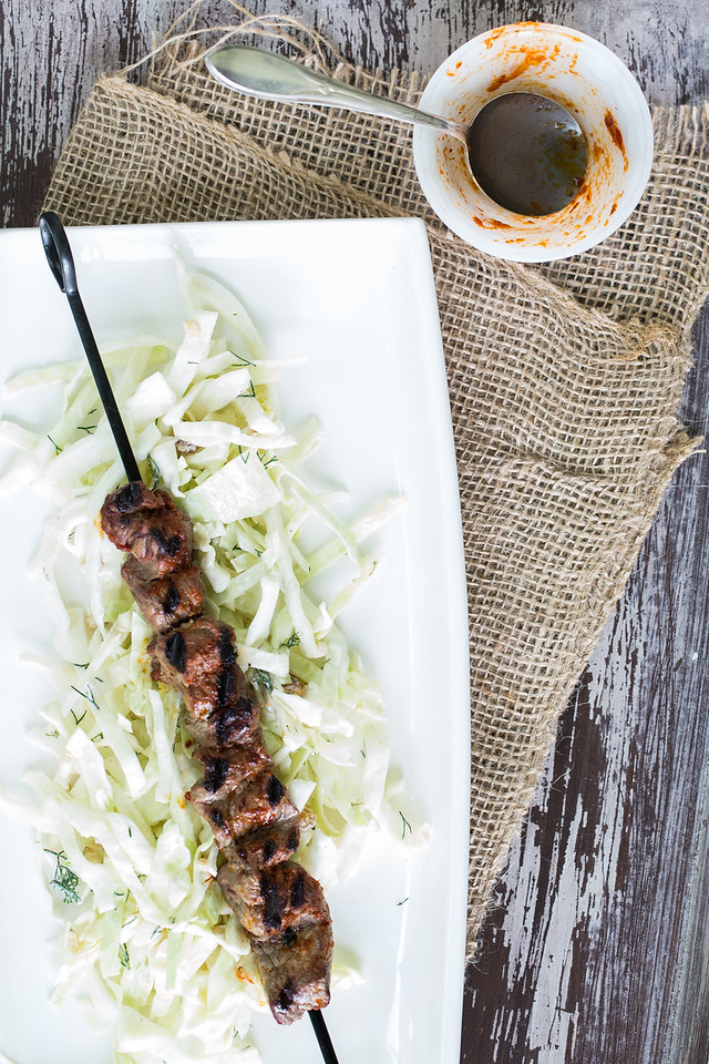 White plate with grilled beef skewers on top of a slaw and empty bowl of harissa marinade