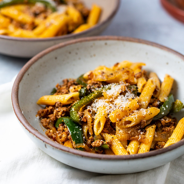 Gray bowl with pasta, bell peppers, sausage topped with grated cheese.
