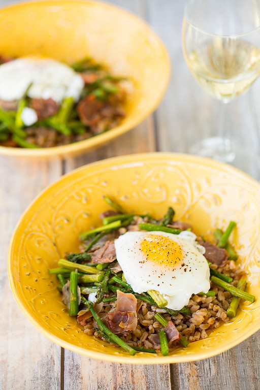 Two grain bowls topped with roasted asparagus, prosciutto and a poached egg.