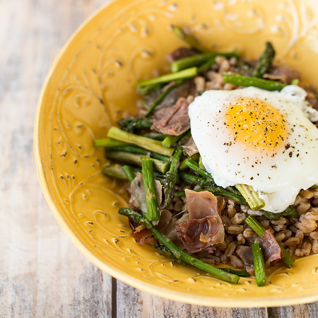 Yellow bowl filled with Roasted Asparagus Grain Salad with a fried egg on top.