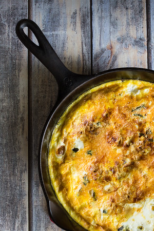 Cast iron skillet with golden frittata on wood background