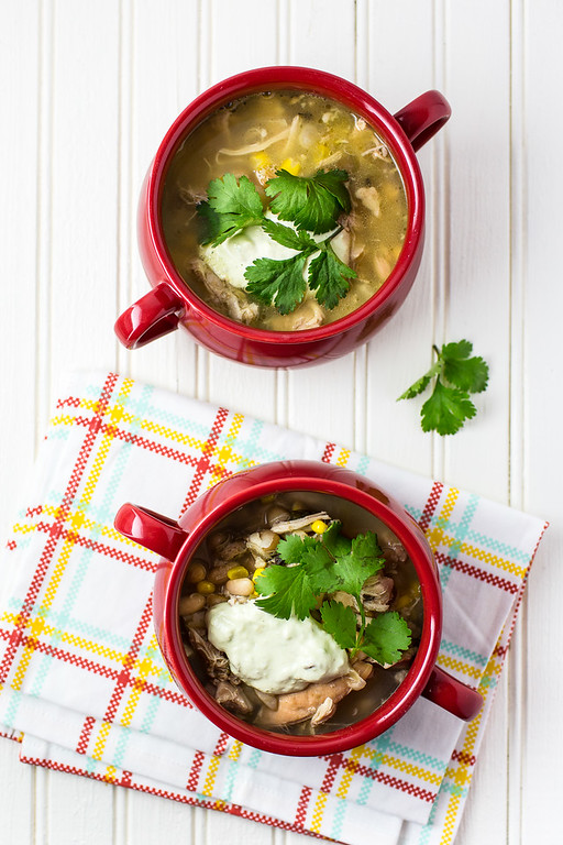 Two red bowls, filled with chili and topped with cilantro and cream.
