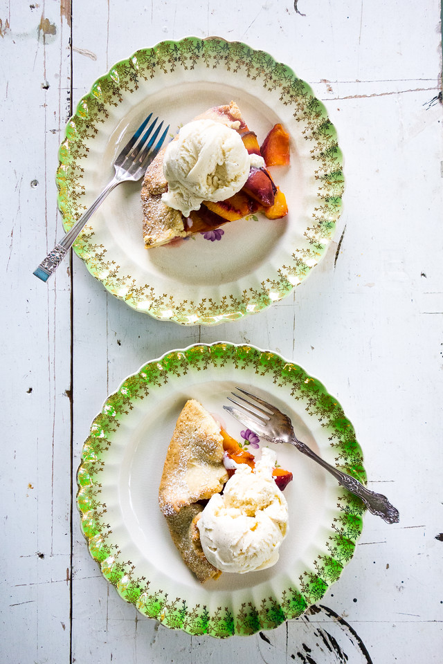 Two plates on a white table with a peach tart topped with vanilla ice cream