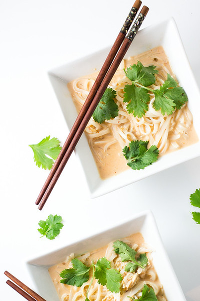 Two bowls of curried noodles with chopsticks and garnished with cilantro leaves.