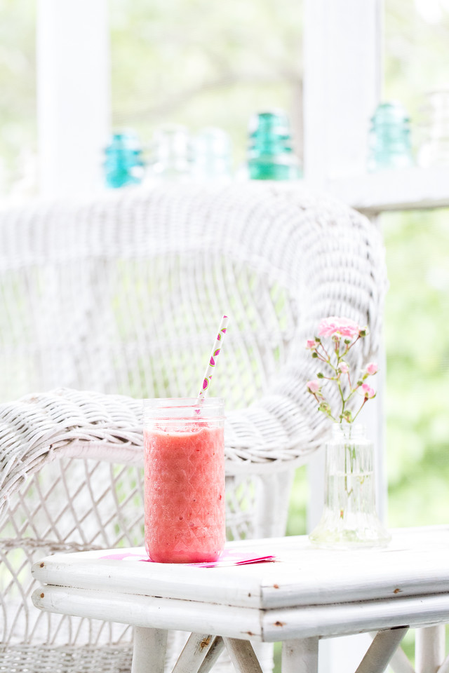glass filled with a pretty pink smoothie on a screened in porch.