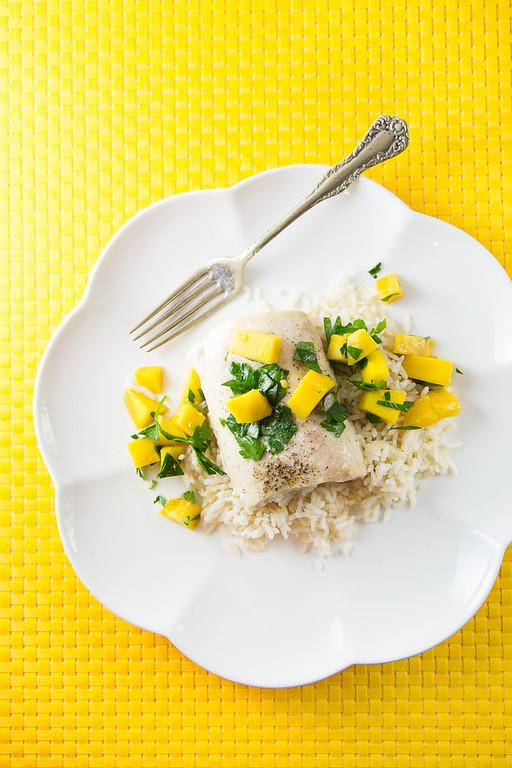 White plate with mango salsa on top of mahi mahi and rice.
