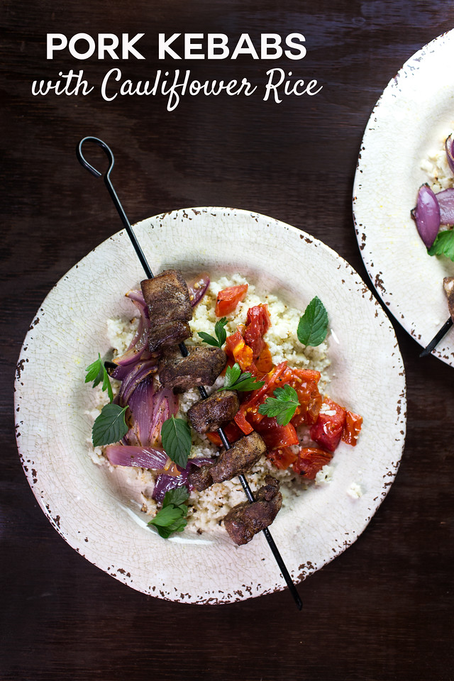 overhead shot of pork kebabs on cauliflower rice with tomatoes and onions.