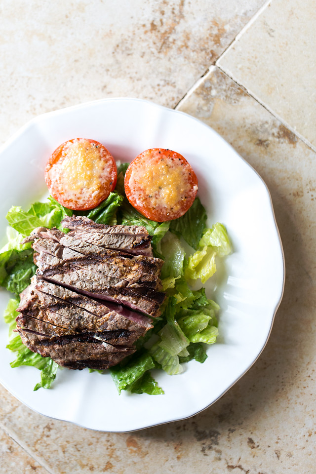 white plate with grilled steak and roasted tomatoes