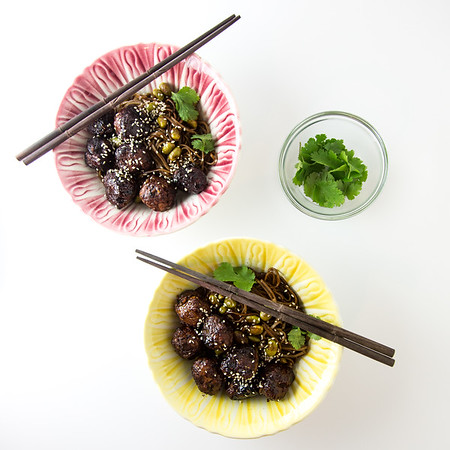 Two bowls filled with meatballs, chopsticks and some cilantro in a bowl.