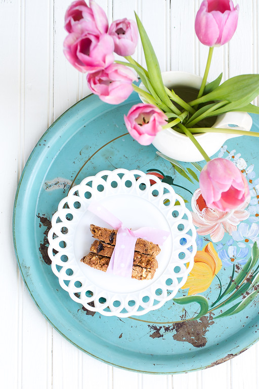 Plate of hazelnut and apricot biscotti on a vintage tray with pink tulips