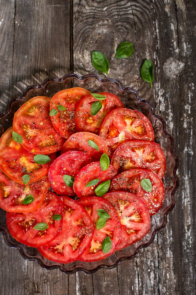 shallow dish filled with sliced tomatoes on wooden background