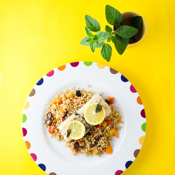 Plate of mahi mahi resting atop a colorful couscous.