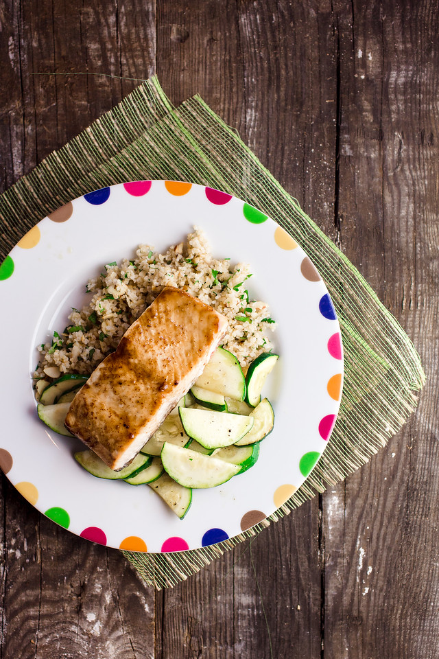 Plate of salmon, zucchini and bulgur pilaf on wooden background