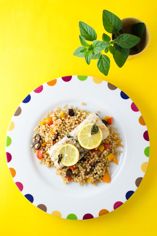 Mahi Mahi with two lemon slices on top rests on a bed of mediterranean couscous.
