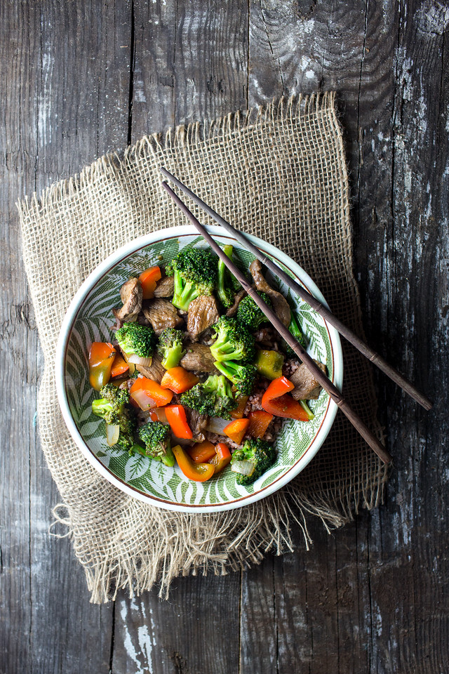 Bowl of beef and broccoli stir fry with red bell peppers and pair of chop sticks on rustic background.