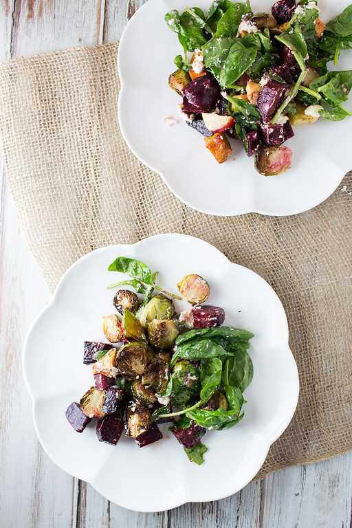Overhead shot of two plates of roasted vegetable salad.