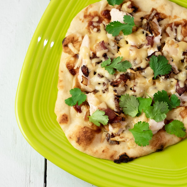Close up a bbq chicken flatbread pizza with cheese and cilantro.