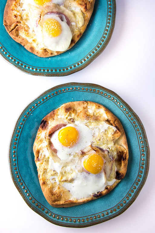 Two blue plates with a flatbread pizza topped with an egg.