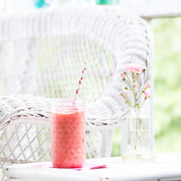 Pink smoothie on a white wicker table.