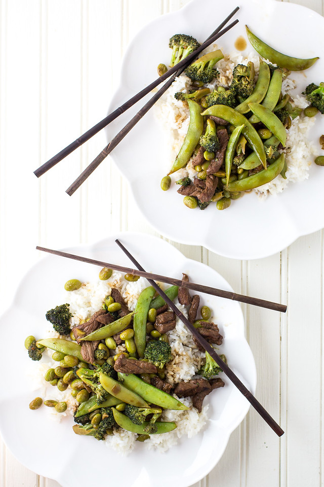 Two plates with a beef stir fry on a white background