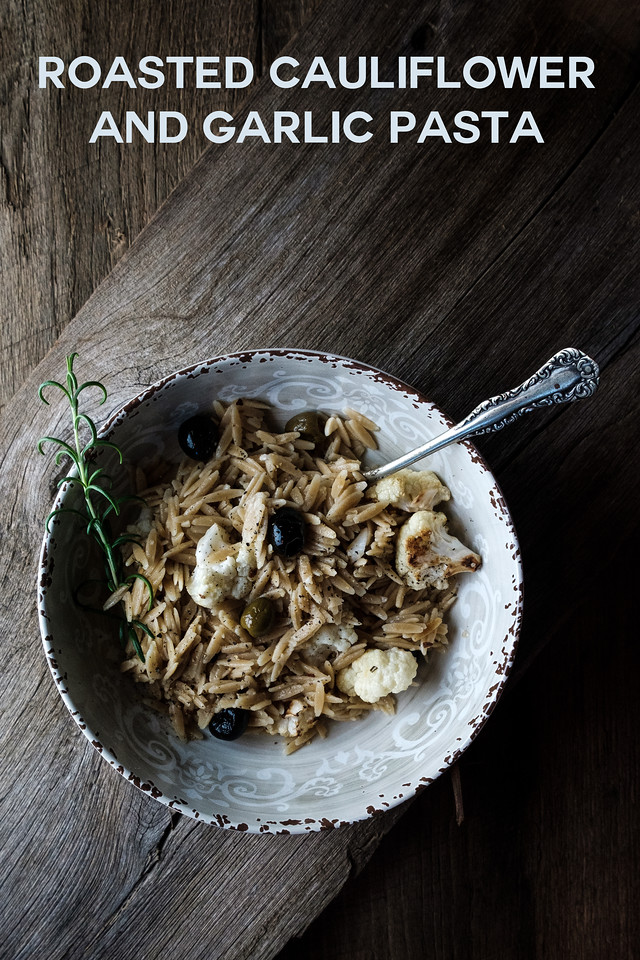Bowl of pasta with cauliflower and olives, on a wooden surface with text overlay reading Roasted Cauliflower and Garlic Pasta