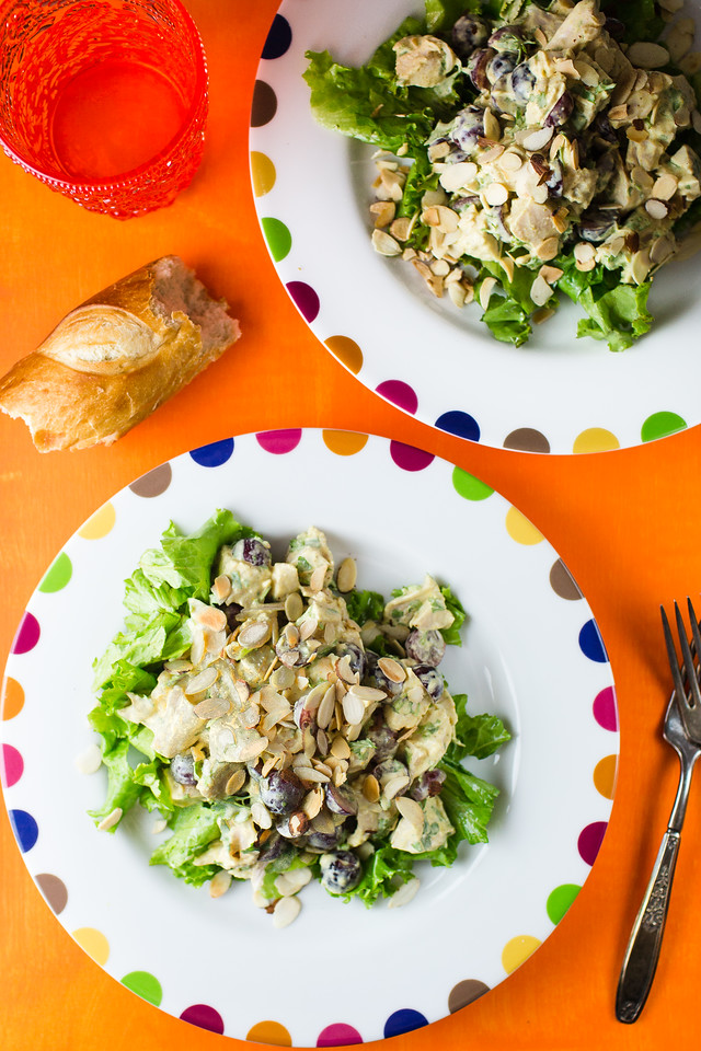 Chicken salad on two plates on an orange background