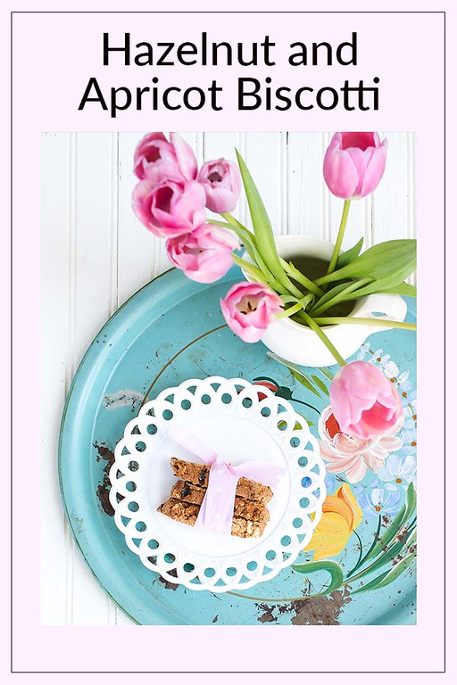 Blue platter with a plate of biscotti and a vase filled with tulips.