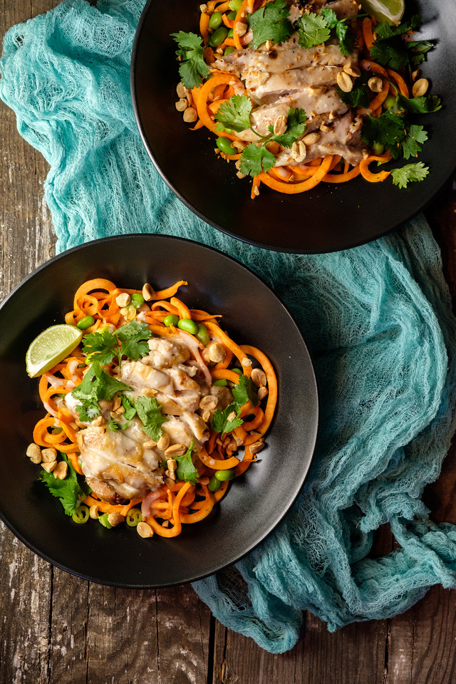 Two bowls of spiralized sweet potatoes with chicken on a wooden background with a teal blue scarf.