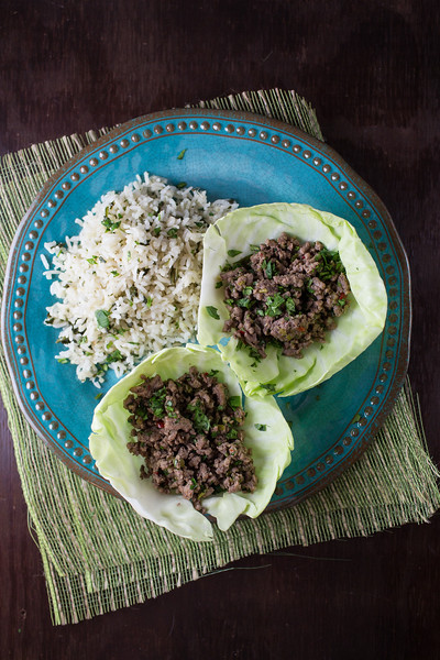 Two thai beef cabbage wraps on a blue plate