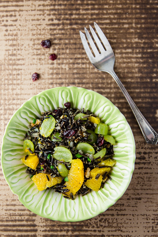 Green bowl filled with Wild Rice Salad with Oranges and grapes.
