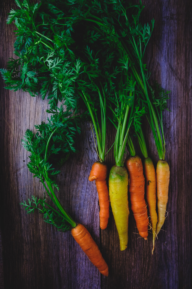 A bunch of orange to yellow carrots with deep green tops