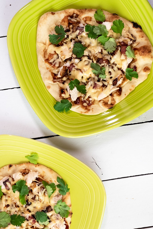 Two plates with flatbread pizzas topped with barbecued chicken and cilantro.