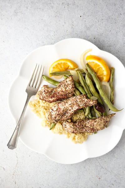 White plate with chicken tenders, green beans and orange slices.