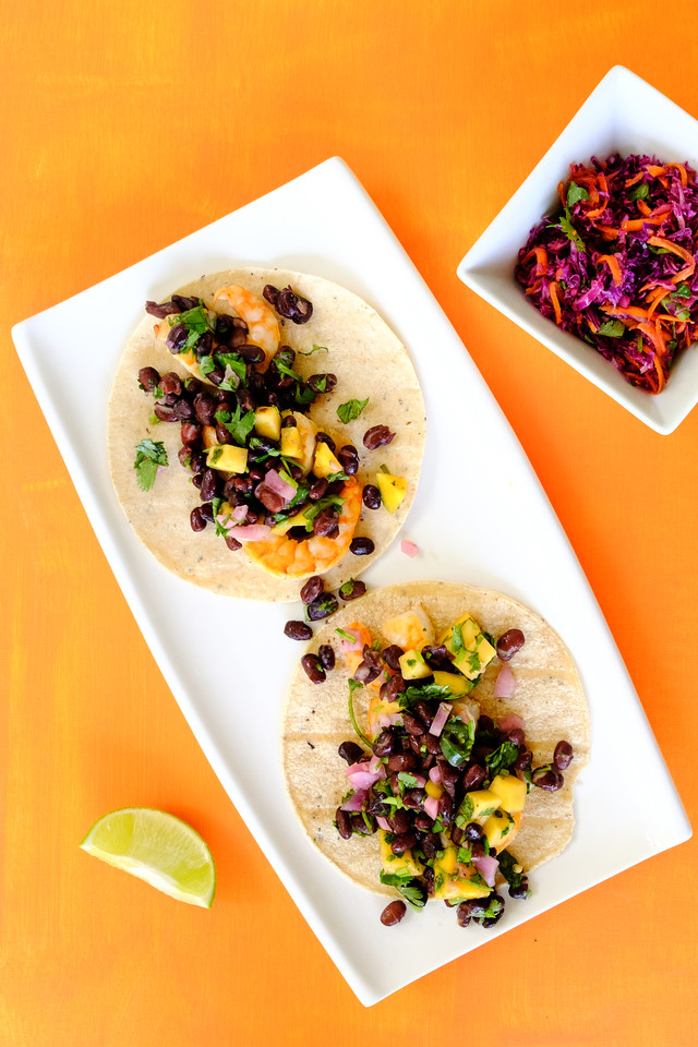 White plate with an over head shot of shrimp tacos with mangoes and black beans