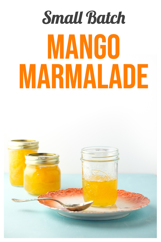 Half empty jar of bright orange mango marmalade on a plate with a spoon and two jars behind it. Text overlay reads Small Batch Mango Marmalade.