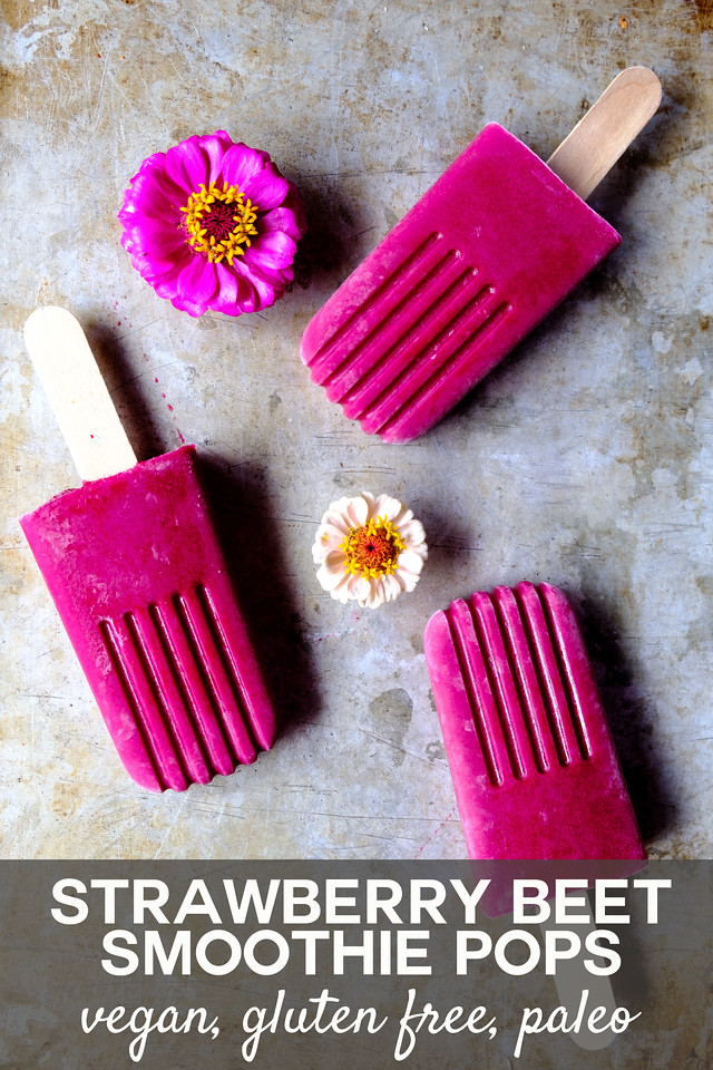 Bright pink popsicles with zinnia flowers on a metal background with text overlay reading Strawberry Beet Smoothie Pops Vegan, gluten free, paleo