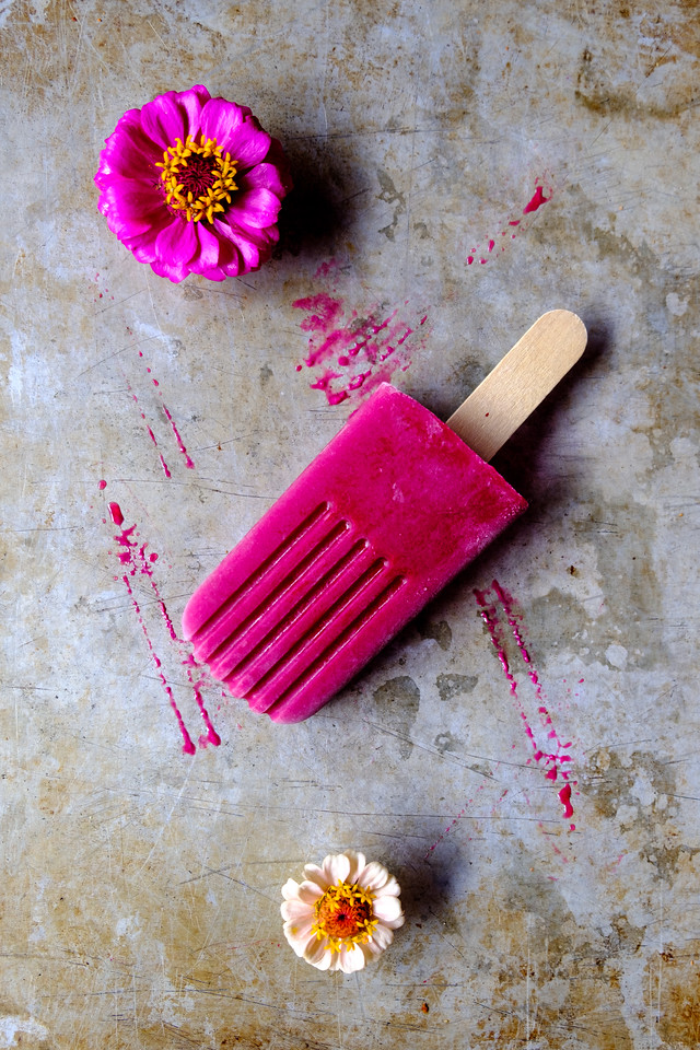 One vibrant pink popsicle on a metal background with zinnia flowers