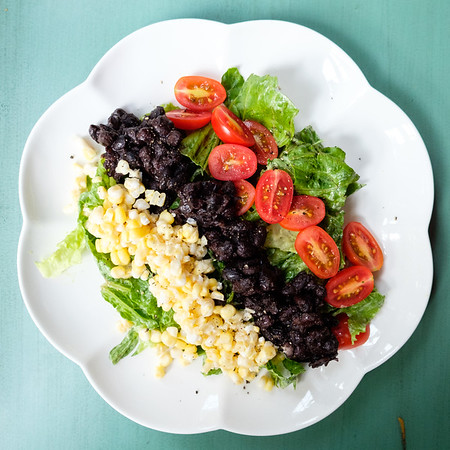 Black Bean Salad with Avocado dressing arranged on a white scalloped plate