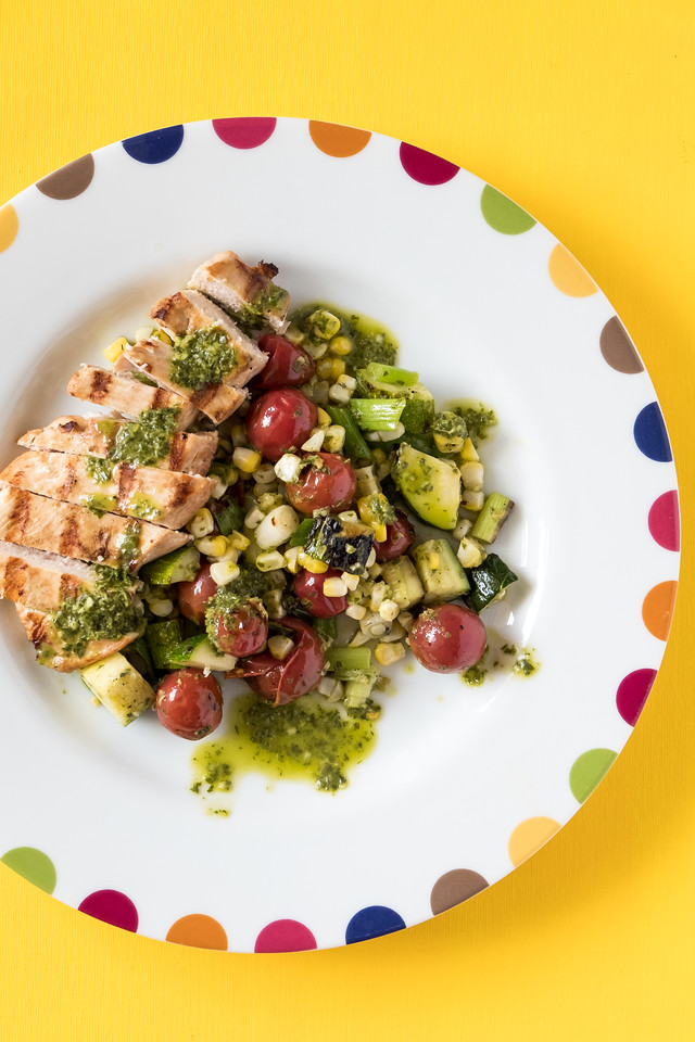 Plate of grilled chicken and vegetables with a green sauce on a bright yellow background.