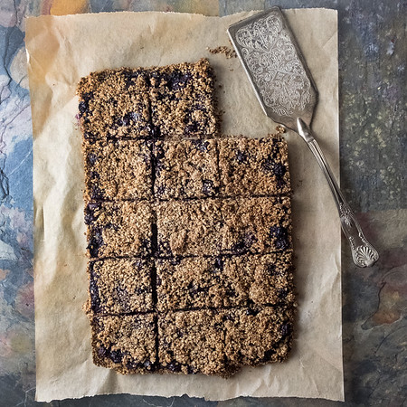 Oat bran blueberry crumble bars laid on parchment paper