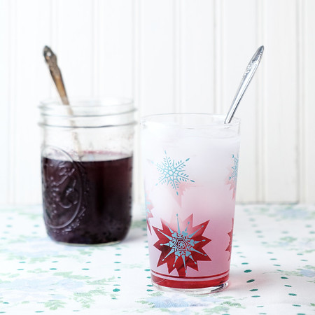 Jar of blueberry shrub and glass of it mixed with sparkling water