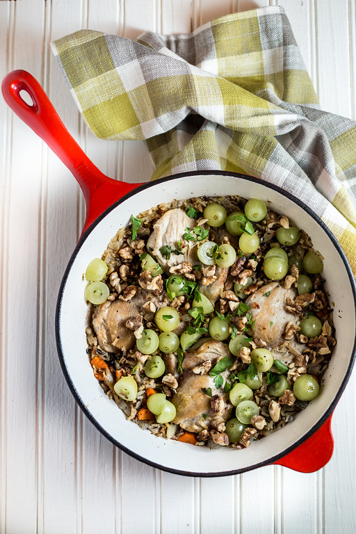 Red skillet with chicken thighs, grapes and wild rice.